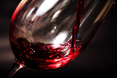 Glass of full bodied red wine being poured. From bottle Stock Images