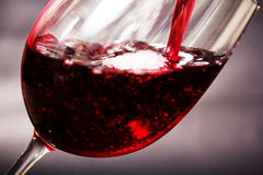 Glass of full bodied red wine being poured. From bottle Royalty Free Stock Photos