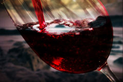 Glass of full bodied red wine being poured Royalty Free Stock Photo