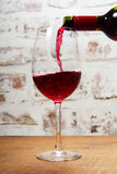 Glass of full bodied red wine being poured. From bottle Royalty Free Stock Image