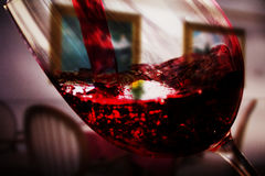Glass of full bodied red wine being poured Royalty Free Stock Images