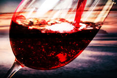 Glass of full bodied red wine being poured Stock Image