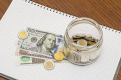 Glass Full of Coins on Egyptian & American Banknotes with Notebook on Wooden Desk royalty free stock photography