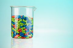 Glass full of color pills Royalty Free Stock Photos
