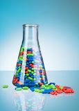 Glass full of color pills and tablets on the floor Stock Images