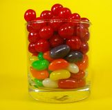 A glass full of colorful candies with a yellow background 3 Royalty Free Stock Image