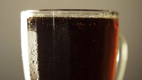 Glass full dark craft beer closeup rotate with drop of condensation cold drink. Beautiful dark craft beer rotating closeup on background. Texture of the stock video footage