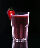 A glass full of juicy, healthy strawberry cocktail on a black background. One-half strawberry with a leaf is on top in a glass cup Royalty Free Stock Images