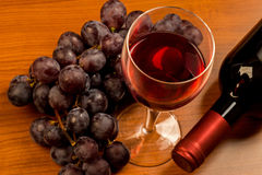 Glass full of red wine with bottle and grapes. On wooden table Royalty Free Stock Images