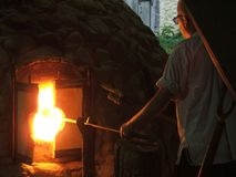 Glass Furnace. Artisan using a reproduction 17th century glass kiln to shape a mouth-blown glass bottleneck royalty free stock photos