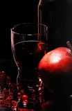 Glass with garnet juice. A pomegranate, grains on a smooth surface in reflected light on a black background Stock Photo