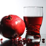 Glass with garnet juice. A pomegranate, grains on a smooth surface stock photography