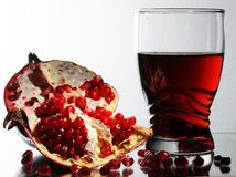 Glass with garnet juice. A pomegranate, grains on a smooth surface Royalty Free Stock Photography
