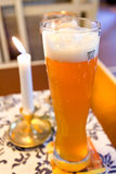 Glass of german beer and lit candle Stock Photos