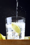 Glass of gin tonic with lime and tonic falling. Glass of gin tonic with a slice of lime and tonic falling Stock Photography