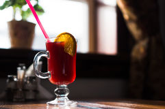 Glass glass with a red drink and lemon stands against the window. With a curtain Stock Image