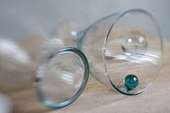 Glass. Es lying on table with small  marbles Royalty Free Stock Photo