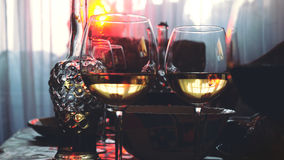 Glass glasses on a table in a restaurant, banquet table, glasses of wine stage red lighting. Stock Photos