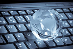 Glass globe. On a laptop keyboard Stock Photos
