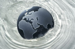 Glass globe. Splashing into water stock illustration