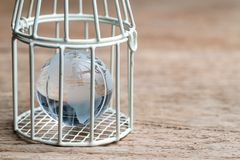 Glass globe with america map inside birdcage on wooden table met. Aphor of limited thinking, underprotection or anti globalization royalty free stock photos