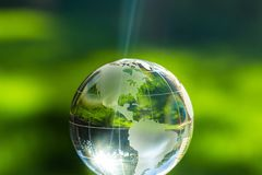 Glass globe ball in light rays on background Stock Photo
