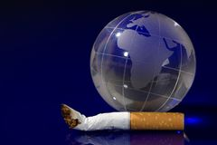 Glass globe with cigarette Stock Photos