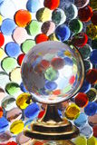 Glass Globe and Colored Glass. Glass globe in front of colorful glass pebbles Stock Images