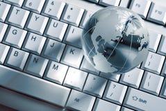 Glass globe on computer keyboard Stock Image