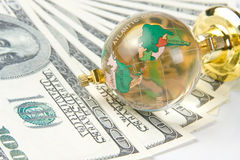 Glass globe and dollars Stock Images