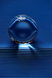 Glass globe or drop of water on a background of blue corrugated paper .Clean and Shine Royalty Free Stock Images