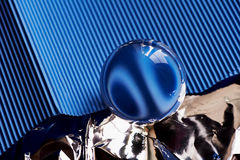 Glass globe or drop of water on a background of blue corrugated paper and foil .Clean and Shine Royalty Free Stock Images