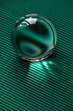 Glass globe or drop of water on a background of green corrugated paper .Clean and Shine Royalty Free Stock Image