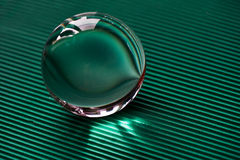 Glass globe or drop of water on a background of green corrugated paper .Clean and Shine Stock Image