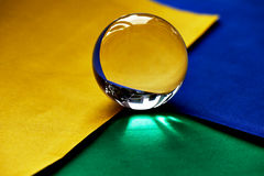 Glass globe or drop of water on a background of green, yellow and blue velvet paper.Clean and Shine Stock Images