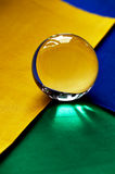 Glass globe or drop of water on a background of green, yellow and blue velvet paper.Clean and Shine Stock Photos