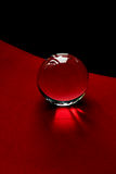Glass globe or drop of water on a background of red and black velvet paper.Clean and Shine Stock Image