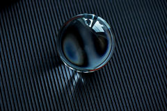 Glass globe or drop of water on a dark graphite corrugated paper .Clean and Shine Stock Photo