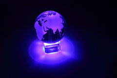 Glass globe at glass stand is illuminated Royalty Free Stock Photo