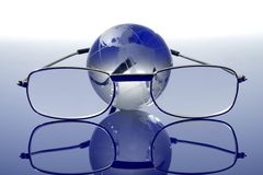 Glass globe with a glasses Royalty Free Stock Photography