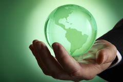 Glass globe. Glass green globe glowing in palm of businessmans hand royalty free stock photos