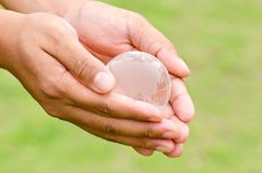 Glass globe in hand Stock Image