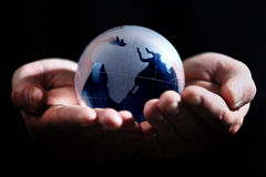 Glass globe in hand Stock Images