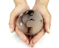 Glass globe in hands Stock Photos