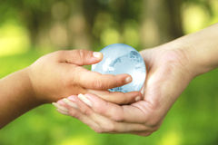 Glass globe in hands Stock Images