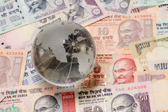 Glass globe on Indian currency Stock Photo
