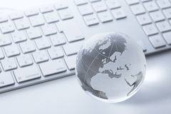 Glass globe on a  keyboard Stock Photo