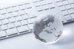 Glass globe on a  keyboard Stock Photo