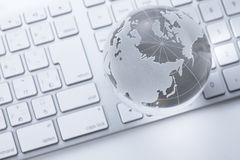 Glass globe on a  keyboard Royalty Free Stock Image