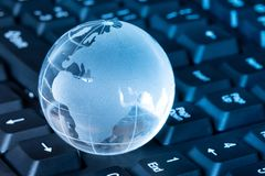 Glass globe on the keyboard. World business and economy Stock Images